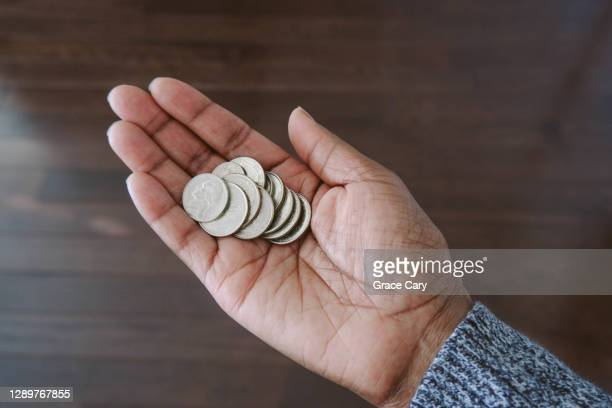 woman holds change in palm of hand - twenty five cent coin stock pictures, royalty-free photos & images