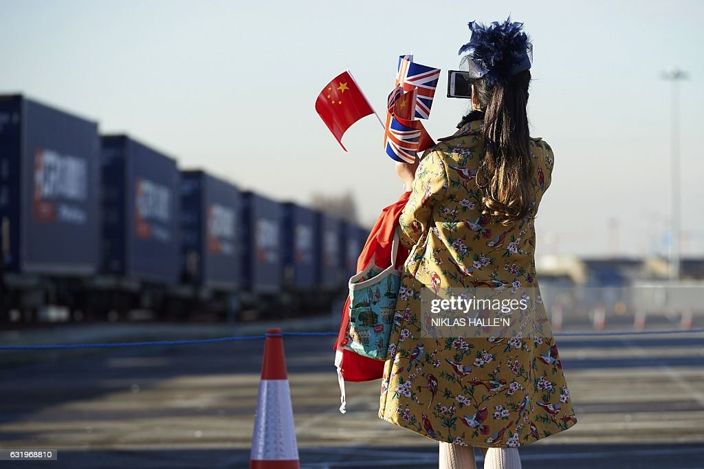 A woman holds Chinese and Union flag as she takes a photo of a freight train laden with goods from China, at DB Cargo's London Eurohub rail freight depot in Barking, east London on January 18, 2017, after it arrived from Yiwu in the eastern Chinese province of Zhejiang. After a journey of 18 days and 12,000 kilometers, the first freight train directly connecting China to the United Kingdom arrived on Wednesday in London. The journey demonstrates Beijing's desire to strengthen its commercial links to Western Europe by reviving the ancient Silk Road, which was used to transport precious merchandise to the Old Continent. / AFP / NIKLAS HALLE'N
