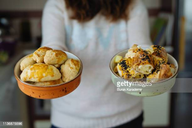 woman holds filled pastries in bowl and turkish patty, börek - cornish pasty stock pictures, royalty-free photos & images