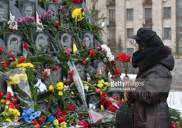 TOPSHOT A woman holds flowers as she stands in front of portraits of slain Euromaidan activists in central Kiev on February 20 2018 Ukraine marked...