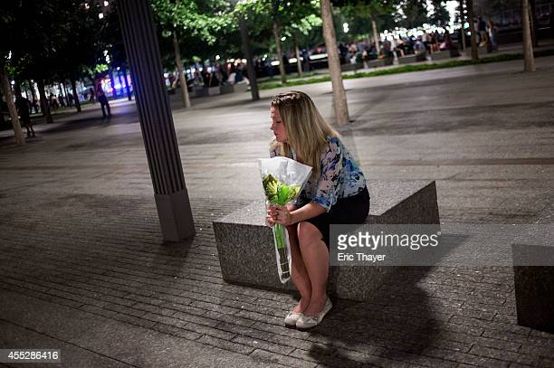 A woman holds flowers at the 9/11 Memorial September 11 2014 in New York City This year marks the 13th anniversary of the September 11th terrorist...