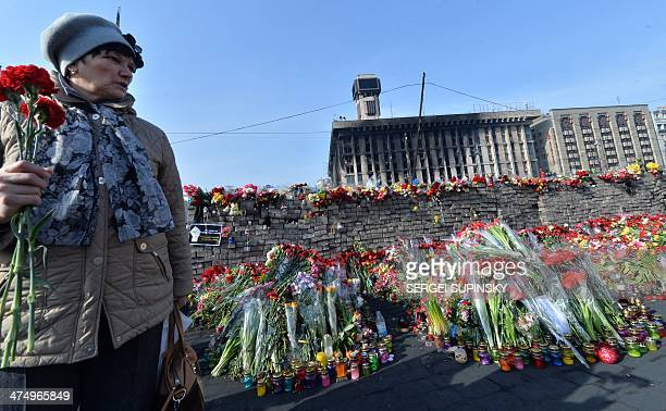 A woman holds flowers near a memorial for protesters who were victims of recent clashes with police at Independence Square in Kiev on February 26...
