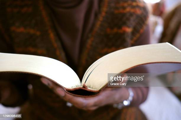 woman holds gilded-edge book - prayer book stock pictures, royalty-free photos & images