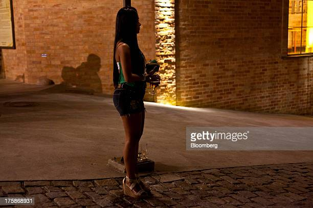 A woman holds glasses of Bebidas das Americas Bohemia brand beer outside a restored Bohemia brewery in Petropolis Brazil Sunday Aug 4 2013 Investors...