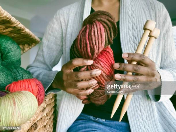 woman holds hand dyed yarn and knitting needles - wool stock pictures, royalty-free photos & images