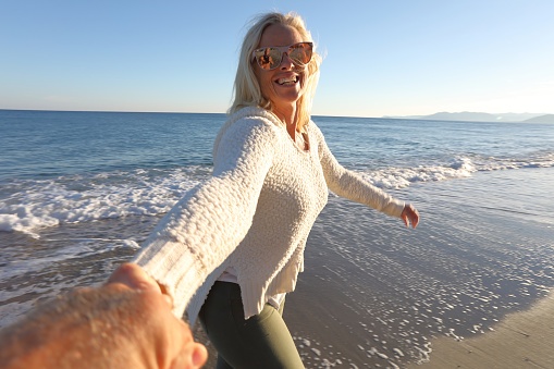 Woman holds hand while running along beach - gettyimageskorea