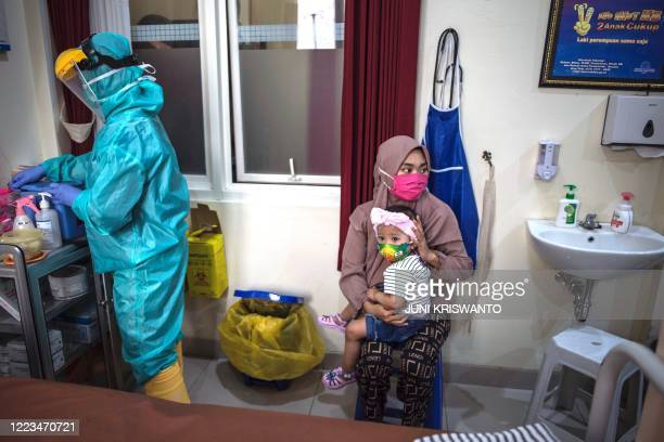Woman holds her baby as a medical staff clad in protective gear prepares the Bacillus CalmetteGuérin vaccine for tuberculosis and oral polio vaccine...