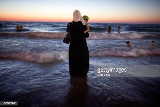 A woman holds her baby as Palestinians enjoy a day at a beach during Eid alFitr which marks the end of the holy month of Ramadan on August 21 2012 in...
