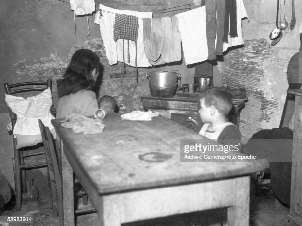 A woman holds her baby as she sits along with a second child at a table in a cramped kitchen Venice Italy 1946