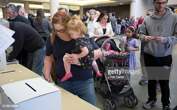 A woman holds her baby as she votesduring the state's Republican caucus on March 5 2016 in Wichita Kansas People were standing in line for more than...