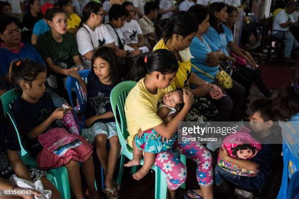 A woman holds her baby during a mass held for victims of the drug war on February 2 2017 in Manila Philippines Philippine president Rodrigo Duterte...