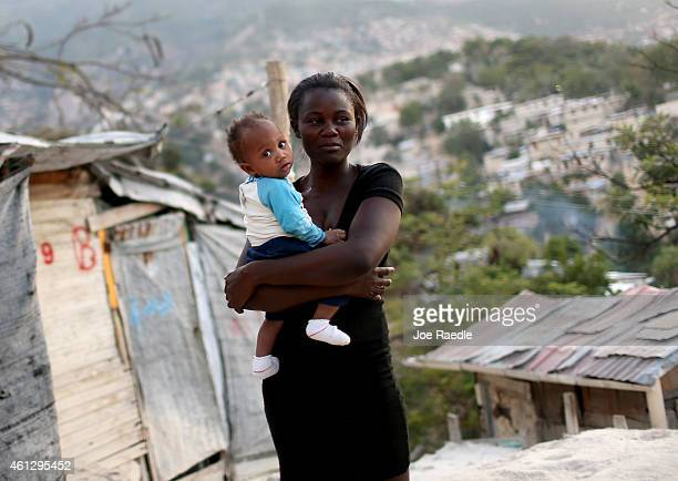 Woman holds her baby near the home made out of tin and tarps that her family built over the land where their home once stood before a magnitude 7.0...