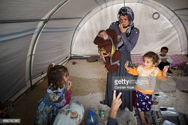 A woman holds her baby surrounded by children in their temporary tent in a refugee camp after crossing from Syria into Turkey in Suruc September 28...