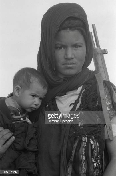 A woman holds her child and a rifle during training of Polisario soldiers in Western Sahara The Polisario is an army dedicated to fighting Moroccan...