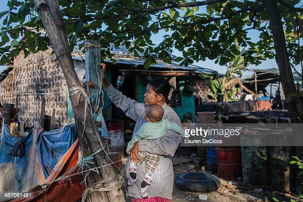 A woman holds her child as she hangs laundry on a clothesline in a temporary oil recycling village on December 16 2013 in Yangon Myanmar Large cargo...