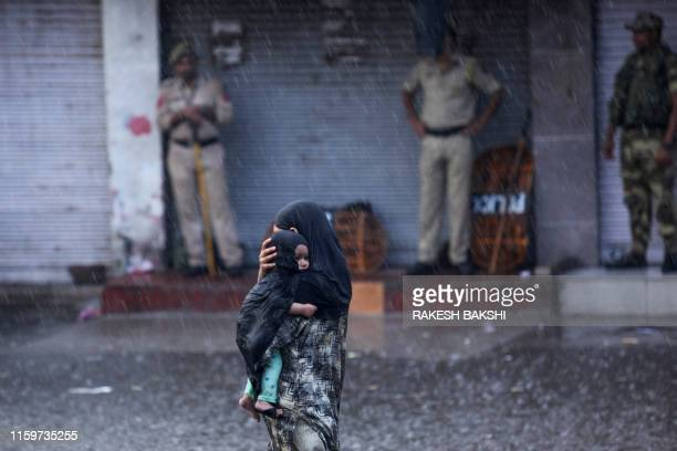 A woman holds her child as she walks past security personnel under rain in Jammu on August 5 2019 Authorities in Indianadministered Kashmir placed...