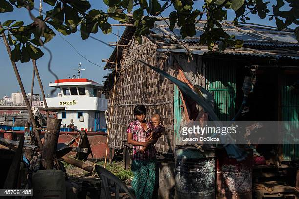 A woman holds her child in a temporary oil recycling village on December 16 2013 in Yangon Myanmar Large cargo ships on the Irrawaddy River in...