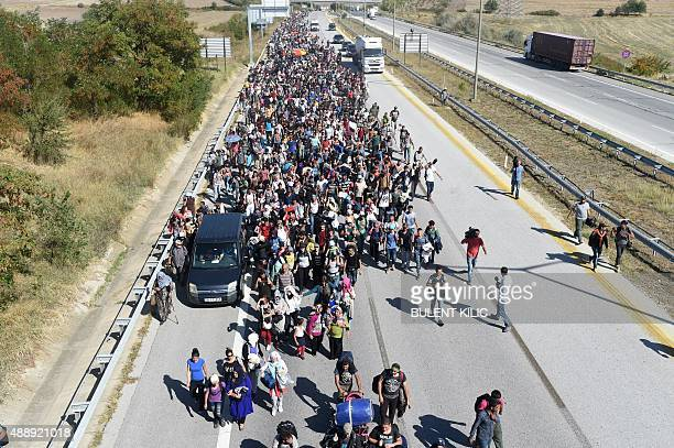 A woman holds her child in front of a line of riot police blocking the route as Syrian migrants and refugees march along the highway towards the...