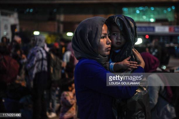 TOPSHOT A woman holds her child wrapped in plastic bag upon their arrival from the island of Lesbos at port of Piraeus near Athens early on October 7...