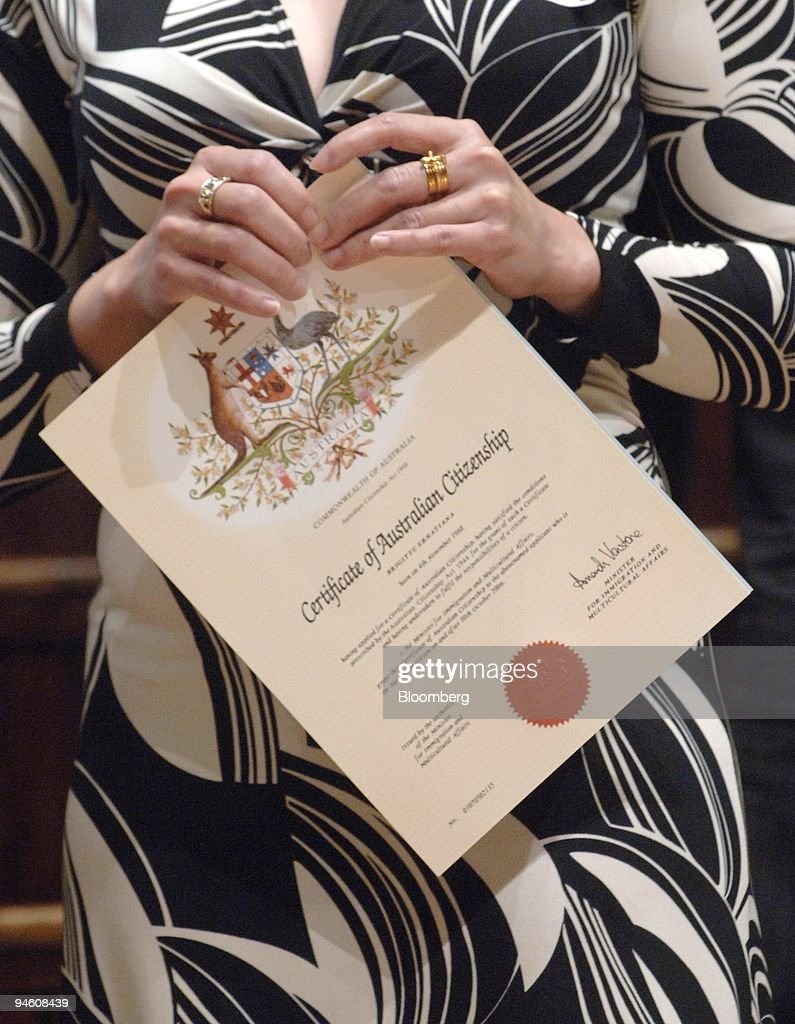 A woman holds her Citizenship Certificate after a ceremony at the Town Hall in Sydney, Australia, on Monday, October 30, 2006.