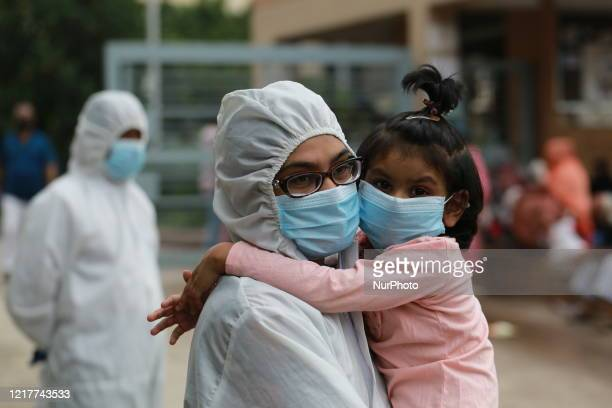 Woman holds her daughter gather outside of the Mugda Medical College and Hospital to get tested for the COVID-19 coronavirus in Dhaka, Bangladesh on...