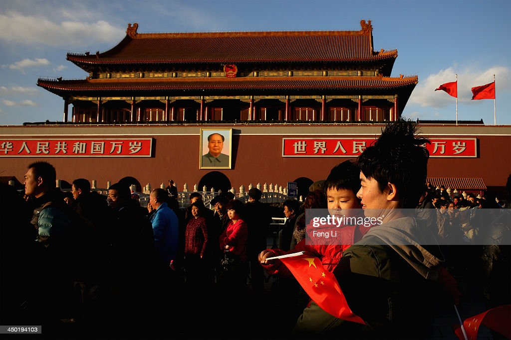 A woman holds her daughter passing Tiananmen Gate on November 17, 2013 in Beijing, China. The full text of the Communist Party of China (CPC) Central Committee's decision on major issues concerning comprehensively deepening reforms was issued on Friday. The decision was approved at the Third Plenary Session of the 18th CPC Central Committee held from November 9 to 12 in Beijing.