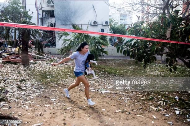 Woman holds her dog as she is running for a shelter after hearing the sirens warning from rockets fired from the Gaza Strip near the site of a rocket...