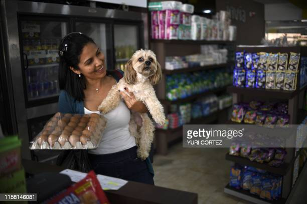 A woman holds her dog while she buys eggs at a Bodegon store which supplies imported basic products with international prices in dollars in Maracaibo...