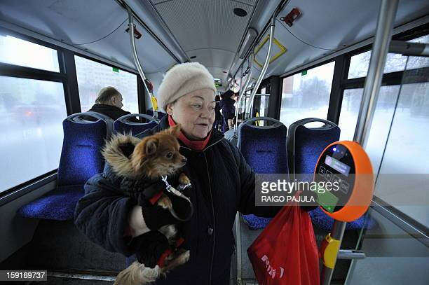 A woman holds her dog while she holds a green special card to a reading device in a bus in Tallinn on January 9 2013 From January 1 residents of the...