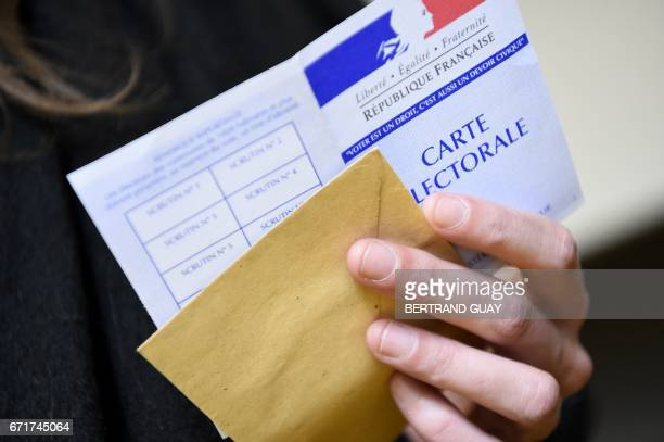 A woman holds her electoral ID card as she arrives to vote at a polling station in Paris during the first round of the French presidential election...