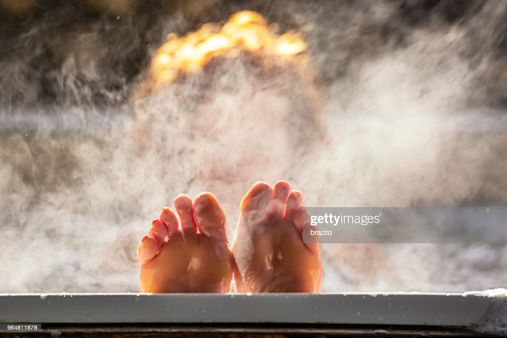 Woman holds her feet up while in a hot tub : Stock Photo