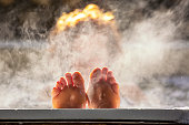 Woman holds her feet up while in a hot tub