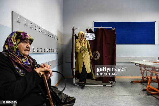 A woman holds her filled ballot as she readies to vote at a polling station in snap twin Turkish presidential and parliamentary elections in Istanbul...