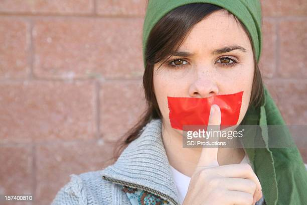 Woman Holds Her Finger To Mouth With Red Tape