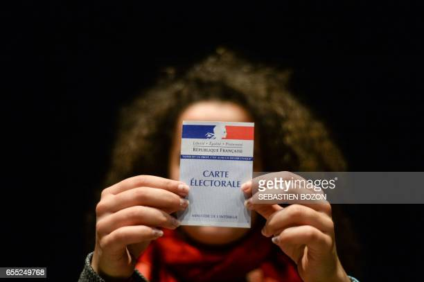 A woman holds her first electoral card on March 19 in Besancon eastern France / AFP PHOTO / Sébastien BOZON