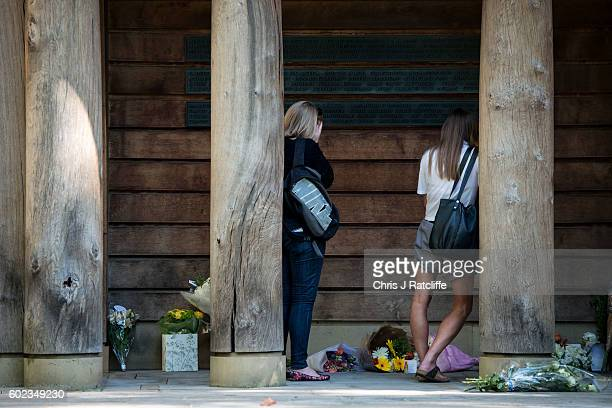 A woman holds her hand to her face before wiping away tears next to floral tributes left by familys and members of the public to victims of the 9/11...