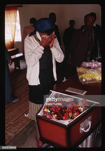 A woman holds her hands over her eyes while crying at a funeral in South Africa