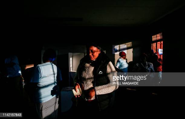 A woman holds her identity document on her way to casts her vote at Rakgatla secondary school polling station during South Africa's national and...