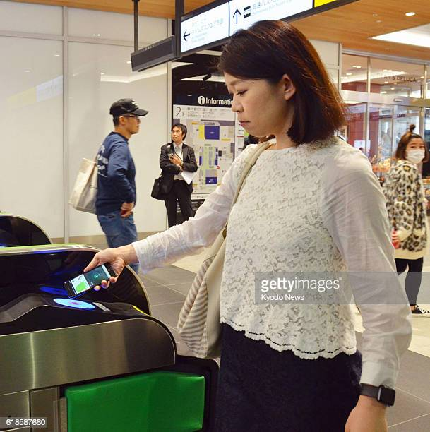A woman holds her iPhone above a card reader at an entrance gate at JR Shinjuku Station in Tokyo on Oct 25 paying for a transportation fee through...