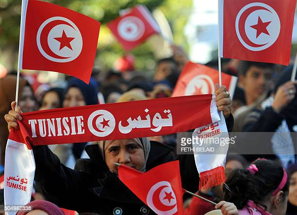 A woman holds her national flag during a rally on January 14 2016 in the Habib Bourguiba Avenue in the capital Tunis to mark the fifth anniversary of...