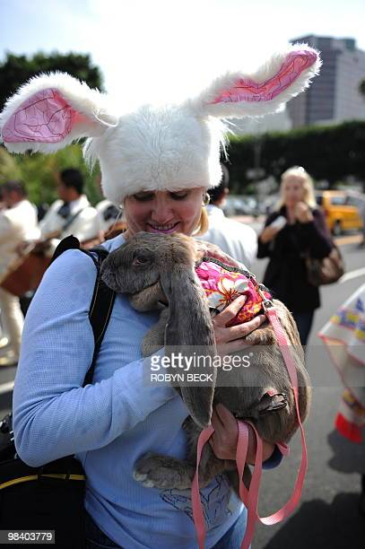 Woman holds her pet rabbit after being sprinkled with holy water by Cardinal Roger Mahony at the Blessing of the Animals at Olvera Street in downtown...