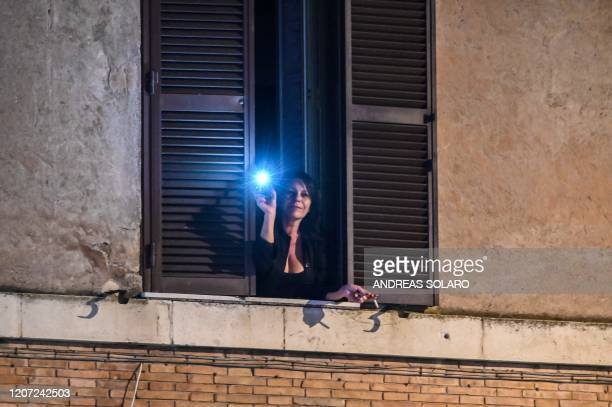 A woman holds her smartphone light out of her window during a flash mob Italia Patria Nostra at the Garbatella district in Rome on March 15 2020...