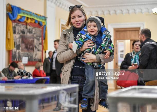 A woman holds her son prior to casting her ballot paper at a polling station during the second round of Ukraine's presidential election in Kiev on...