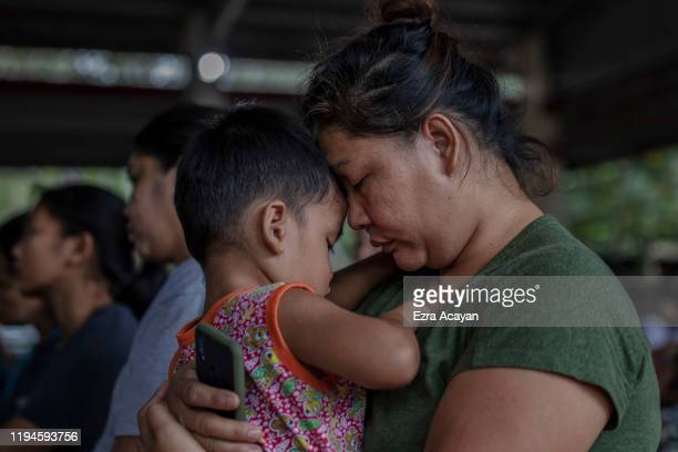 A woman holds her son while attending Sunday mass at an evacuation center for residents who fled Taal Volcano's eruption on January 19 2020 in Lipa...