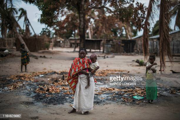 Woman holds her younger child while standing in a burned out area in the recently attacked village of Aldeia da Paz outside Macomia, on August 24,...