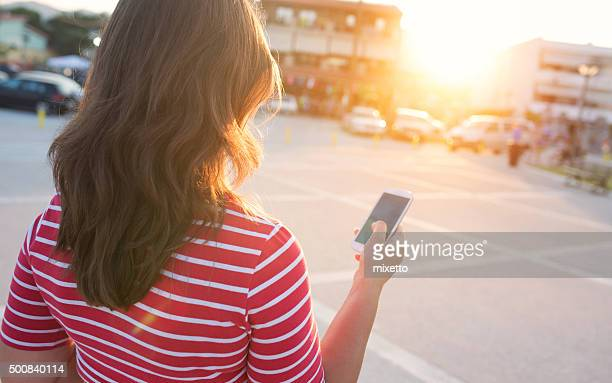 Woman holds in her hand a smartphone outdoors