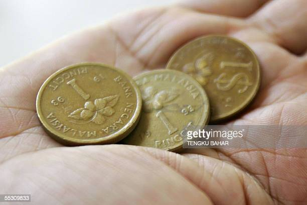 A woman holds in her hand one ringgit coins produced in the early 1990s in Kuala Terengganu 07 September 2005 A move by the Malaysian central bank to...
