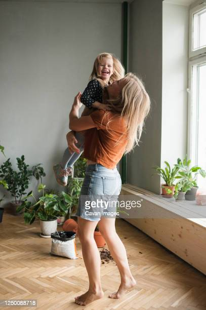 woman holds in hugs her laughing child in living room with lot plants - comfortable stock pictures, royalty-free photos & images