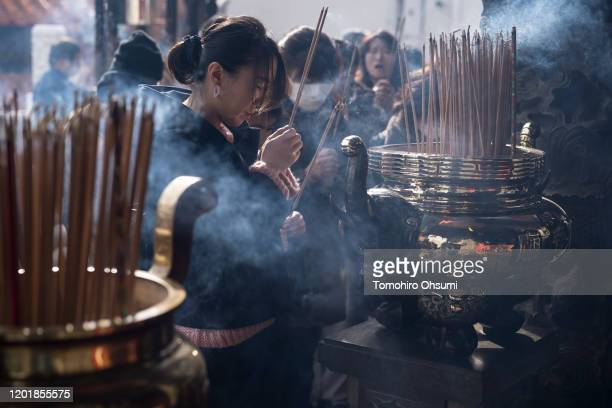 Woman holds incense as she prays at a temple in Yokohama China Town on on January 25, 2020 in Yokohama, Japan. Thousands of people gathered in the...