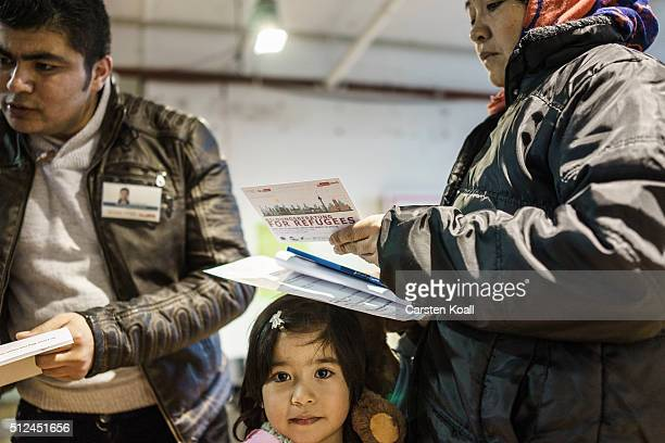 A woman holds information brochures at a new jobs counseling center for migrants and refugees at former Tempelhof Airport on February 26 2016 in...